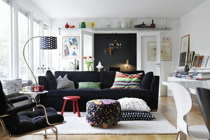 salon con sillón y sofá en negro, paredes blancas, tapete, taburete rojo, escritorio con libros y cuadros, ventanas sin cortinas, jarrones de vidrio en verde, rojo y amarillo, decoracion nordica salon