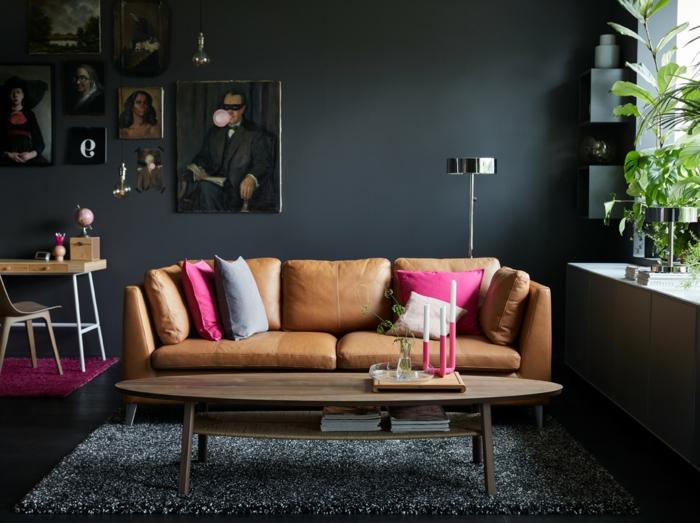 habitación gris, salón con sofá de cuero, cojines color ciclamen, paredes en gris pizarra oscuro, retratos al oleo, suelo laminado, tapete