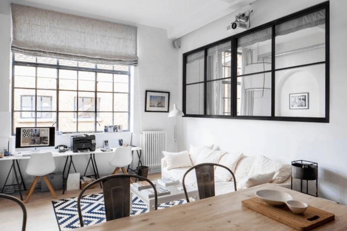 salon nordico, pared con espejo grande con marco negro, escritorio con dos sillas, sofa blanco, tapete con rombos, mesa de madera con sillas de metal, ventana con cortina de lino