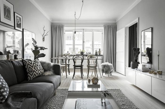 decoracion en gris, blanco y negro, estilo nordico, salon comedor, suelo con tarima, cortinas masivas, bombilla colgante, paredes con fotografias, sofa con cojines y cubierta de lana, mesa grande