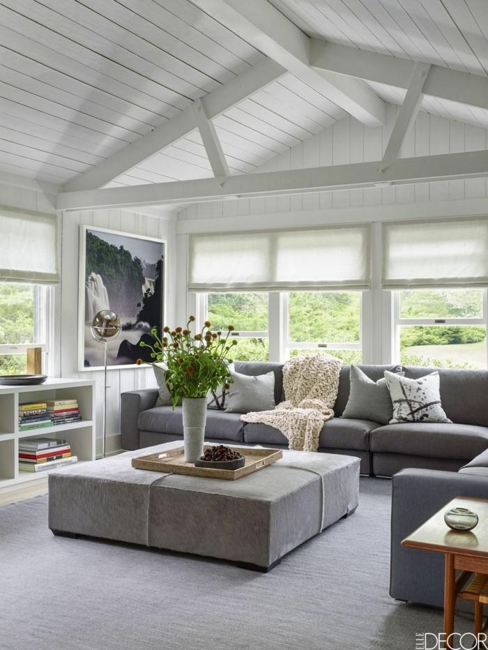precioso salón colocado en una buhardilla, techo en blanco con vigas de madera, muebles de salon modernos en gris