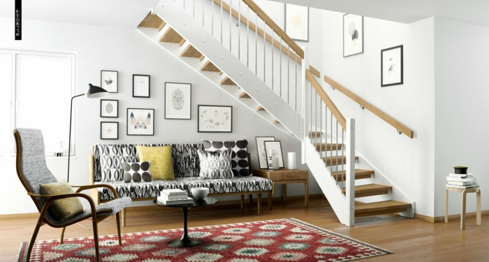 casa con escalera, cuadros en marcos negros, sofá con cojines en figuras geométricas, alfombra en rojo, sillón y mesita de café redonda