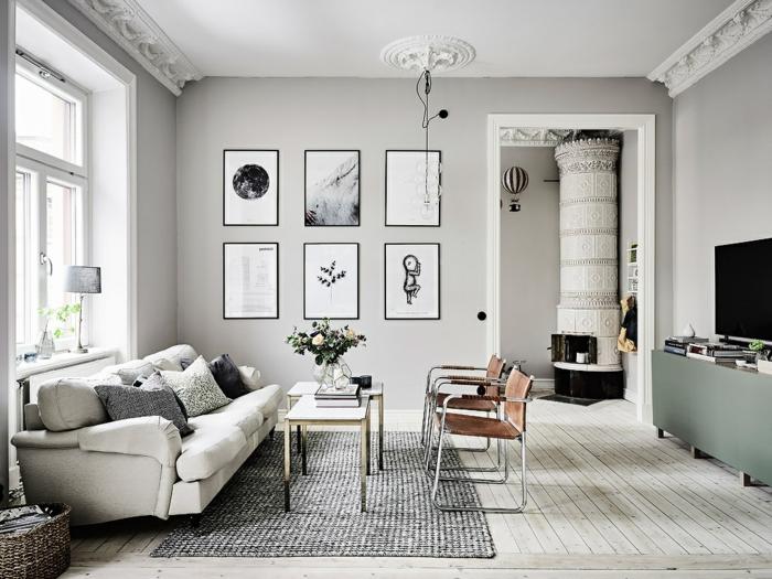 colores que combinan con gris, salon grande estilo escandinavo, chimenea antigua grande,suelo con tarima, luz natural, cuadros en blanco y negro, mesita con rosas, sofá con cojines, tapete