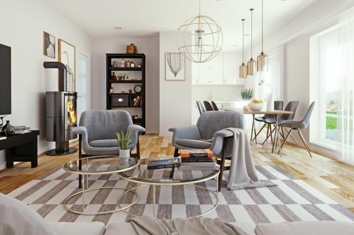 sala de etsar con chimenea, sillones grises, decoracion estilo nordico, estantería negra, tapete en rayas, mesa grande rectangular con sillas de plástico, ventanales, suelo con tarima