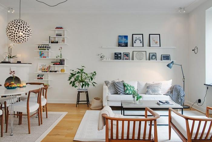 sparedes blancas, salon comedor, casas nordicas, estantes con cuadros en marcos negros, mesa baja rectangular, mesa comedor ovalada