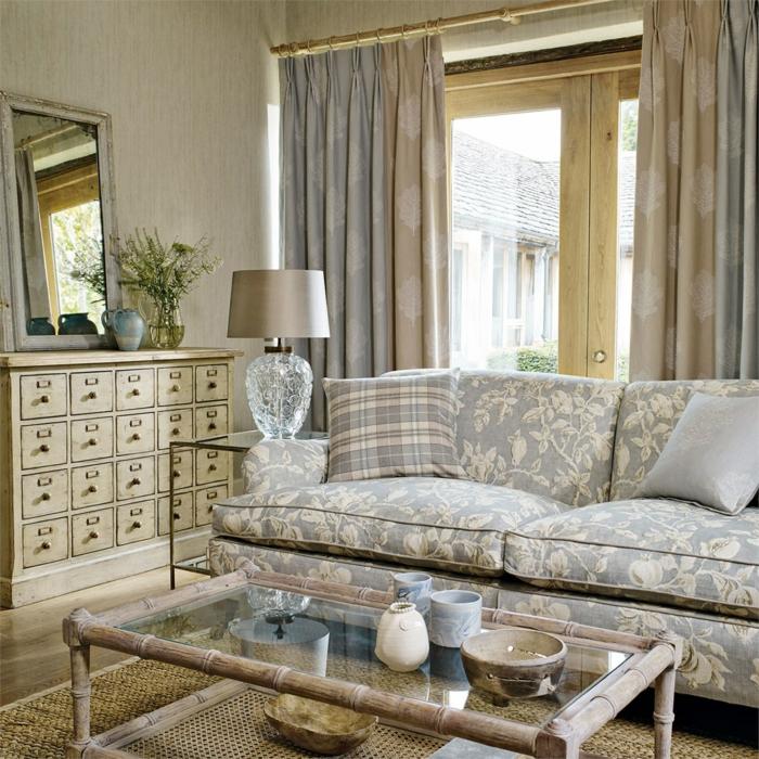 decoracion vintage salon, sofá con motivos florales, colores para habitaciones, ventana con cortinas, espejo, tapete de mimbre, mesa de bambu y vidrio