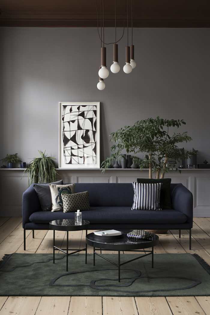 ideas de decoracion moderna, salon con suelo de tarima, sofá tapizado azul navy, habitacion gris, tapete, mesitas bajas redondas, cuadro en blanco y negro