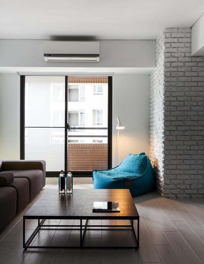 interior en estilo minimalista con diseño sencillo, pared de ladrillo con puf en color turquesa y suelo de parquet