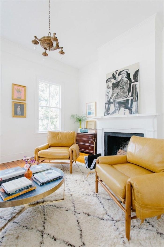 estilo nordico, salón con chimenea y sillones tapizados de cuero, lámpara de araña, pinturas, ventana pequeña, tapete peludo en rombos