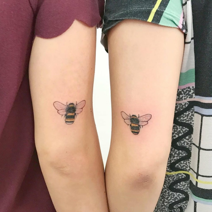 tatuaje de color, tatuajes de familia, diseños iguales para hermanas, brazo con abeja pequeña en colores, mujeres con mangas cortas
