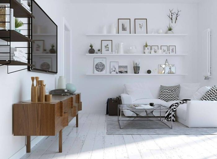 elementos mitad de siglo, mueble auxiliar bajo de madera, televisor grande, decoracion nordica salon, estantes con cuadros y jarrones decorativos, sofá blanco con cojies cheurón, mesa de metal y vidrio