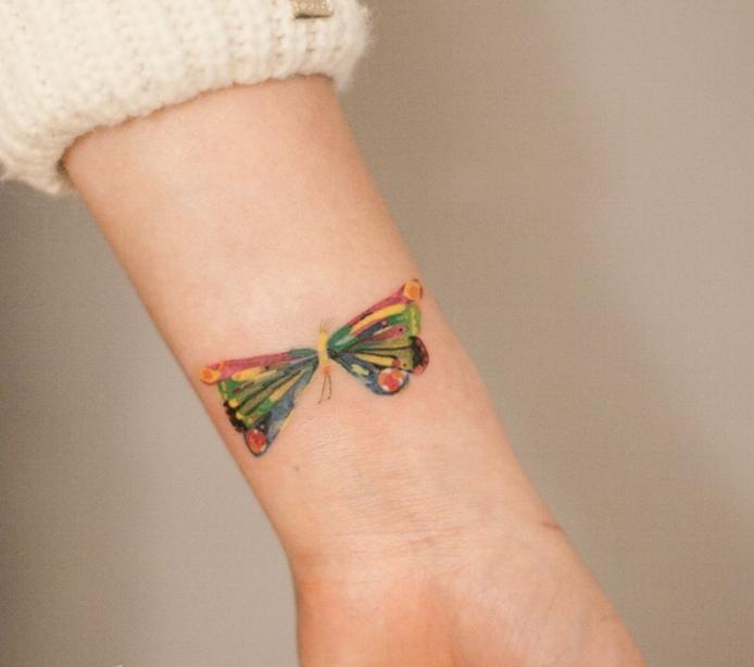tatuaje de mariposa de colores, rojo, amarillo y verde, mujer tatuada muñeca, jersey blanco, tatuajes pequeños originales,