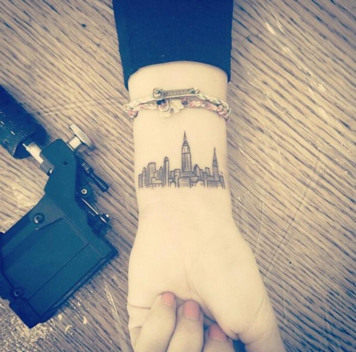 mujer con uñas pintadas y pulseras, tatuaje en la muñeca con edificios urbanos y rascacielos, tatuajes pequeños originales