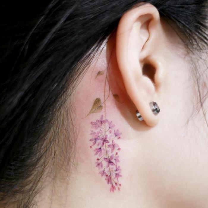 tatuaje de flores detrás de la oreja, mujer con pendientes, flor morada, tatuaje acuarela, tatuajes pequeños