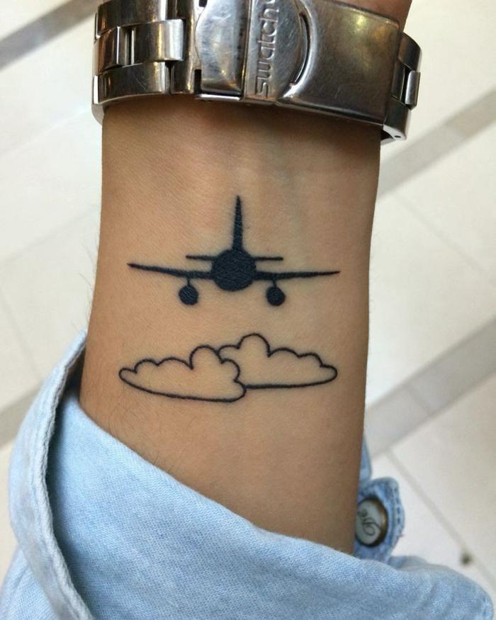 tatuaje estilo animación, mano con reloj y camisa jeans, avion volando sobre nubes, blanco y negro, tatuajes originales