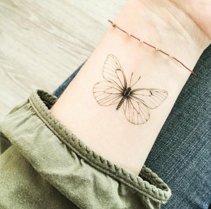 idea de tatuaje femenino, tatuajes en la muñeca, mano con pulsera con hilo, mariposa en blanco y negro, manga verde
