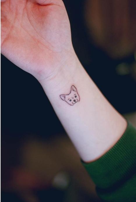 idea de tatuaje para mujeres, mano con manga verde, cara de perrito pequeño, tatuaje minimalista, tatuajes flechas