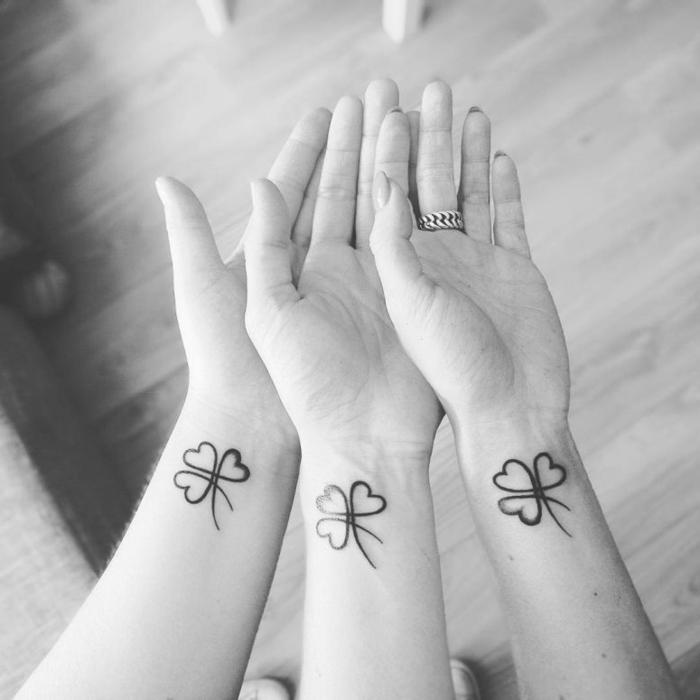foto en blanco y negro, tatuajes iguales para hermanas, simbolos que signifiquen familia, tatuaje trébol en la muñeca