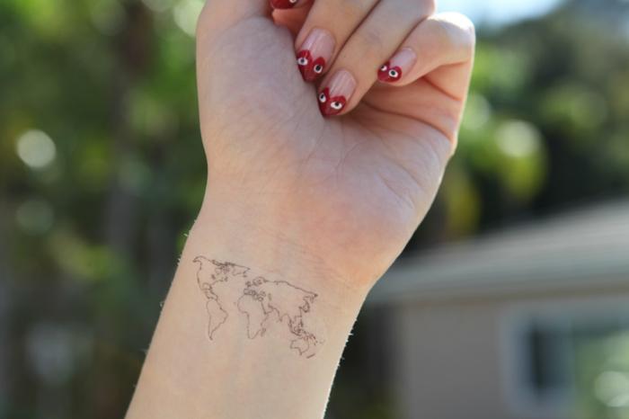 mano de mujer con manicura en rosa y rojo, tattoos pequeños, tatuaje minimalista delicado mapa mundo,