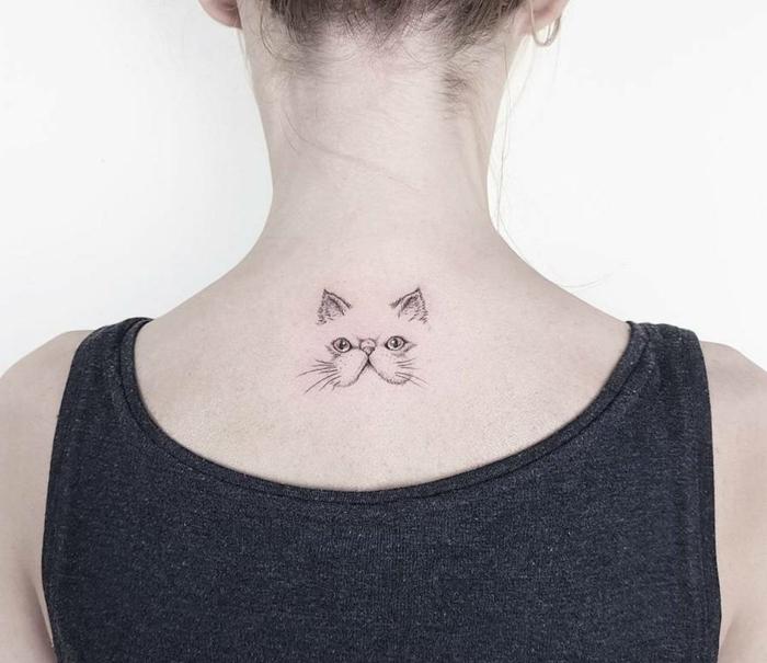 mujer con pelo recogido, tatuaje en la espalda, blusa negra, tatuajes elegantes, cara de gato