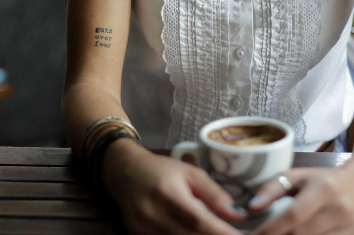 frase inspiradora, tatuaje brazo mujer, mujer con blusa blanca, tacita de café, fondo máquina de escribir, tatuajes pequeños mujer
