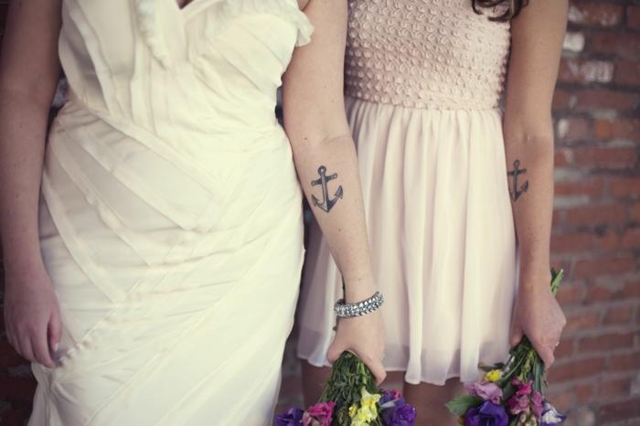 vestido de boda, mujeres con ramos de flores, tatuajes iguales en el antebrazo, ancla grande, simbolos que signifiquen familia