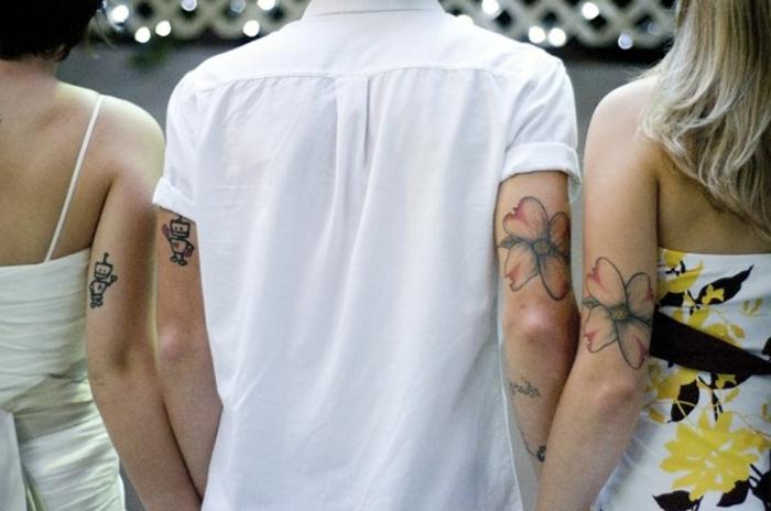 dos hermanas y un hermano, tatuajes similares en el brazo, robots y flores en negro y rojo, mujeres con vestidos, hombre con camisa blanca