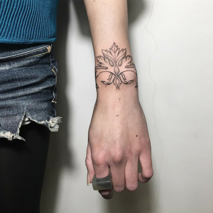 mujer con jeans cortos, mano con anillo, tatuaje en la muñeca delicado con motivos florales tipo brazalete, tatuajes de nombres en la muñeca,