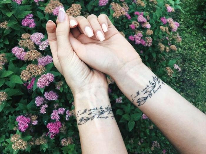 simbolo de familia, tatuajes de hermanas iguales en la muñeca, frase en cursiva y hojas de flores, manos femeninas con manicura, flores en rosado