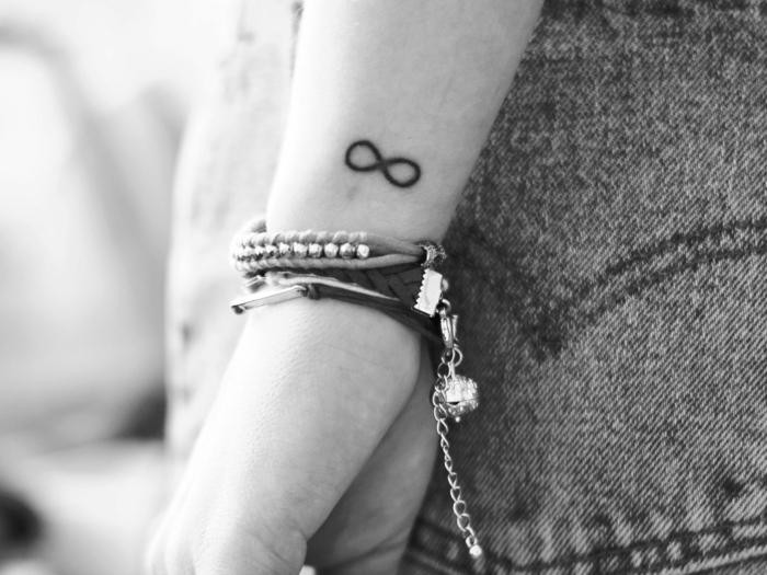 foto en blanco y negro, mujer con jeans y pulseras, tatuaje símbolo del infinito negro, tatuajes en la muñeca