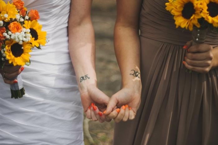 muñecas tatuadas con iniciales, mujeres con ramos de girasoles, uñas color naranja, tatuajes familia simbolos