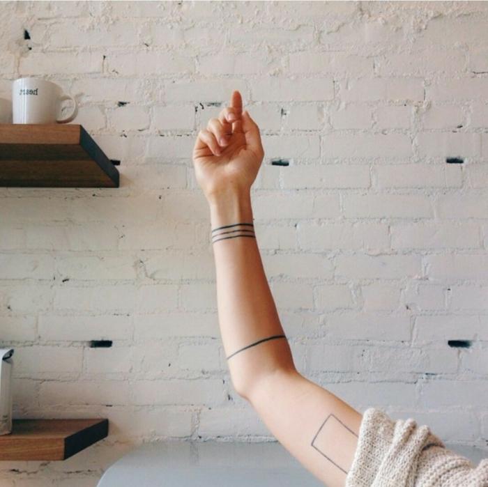 tatuajes en el brazo, brazaletes negras minimalistas, brazo mujer, fondo con pared de ladrillo visto, tatuajes minimalistas