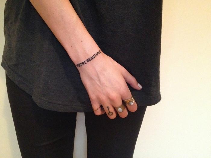 tatuaje de frase, tatuajes minimalistas, muñeca de mujer, dedo con tattoo de llave, anillos, you are beautiful