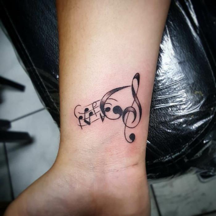 tattoo en la muñeca, tatuaje pequeño de pentagrama con notas y claves sol y fa, tatuaje recién hecho, blanco y negro