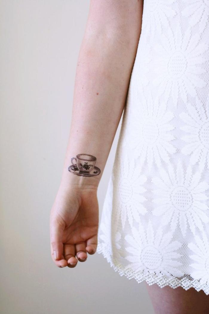 diseño tatuaje divertido, mujer con vestido blanco corto, taza de té en la muñeca, blanco y negro, tatuajes flechas