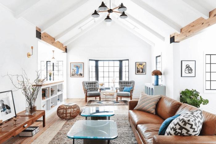 salon grande, ventana sin cortinas, mucha luz natural, estilo nórdico, mesitas de café con encimera de vidrio, sillones en capitoné color gris, sofá de cuero, alfombra y cuadros
