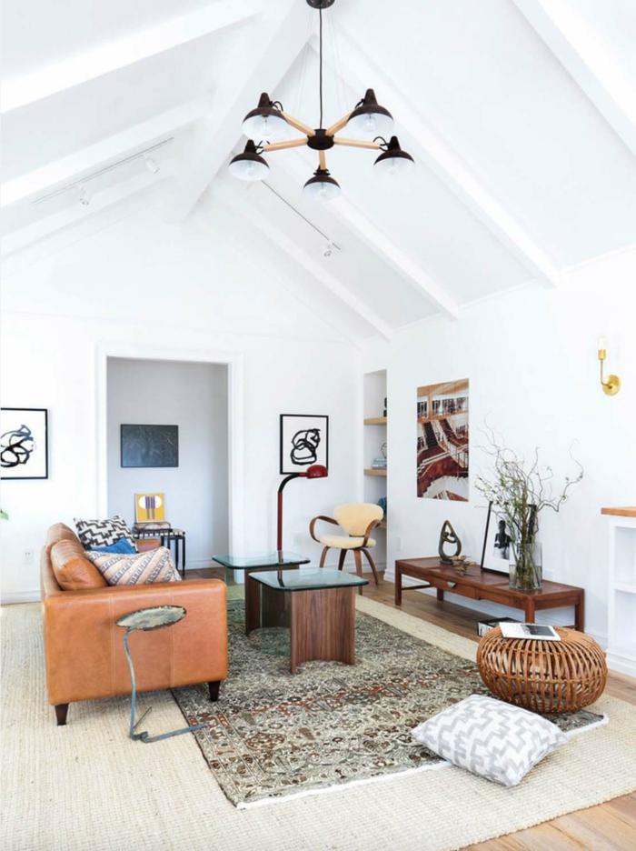 salón moderno grande, estilo nórdico, techo triangular, sofá tapizado de cuero, alfombra persa, paredes blancas, mesas bajas de madera oscura, cuadros y librería en nicho