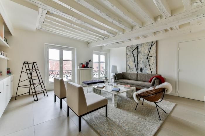 sala de estar grande con mesita cuadrada de m;armol, muebles estilo nordico, suelo con baldosas, decoracion en beige y gris, silla acapulco, techo con vigas de madera pintadas, escalera
