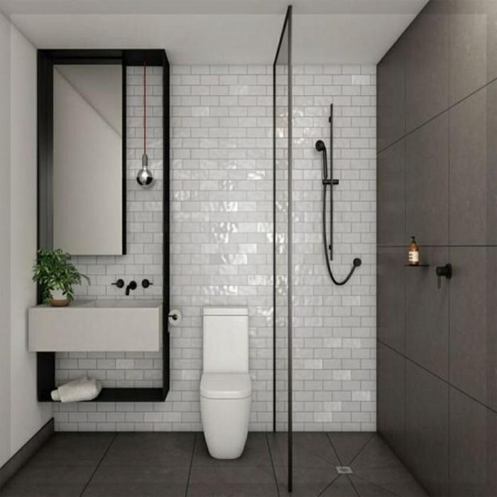 cuartos de baño pequeños, decoracion en blanco y negro con pared de ladrillo visto esmaltado, baldosas en gris pizarra, ducha con mámpara de vidrio, bombilla colgante y planta verde