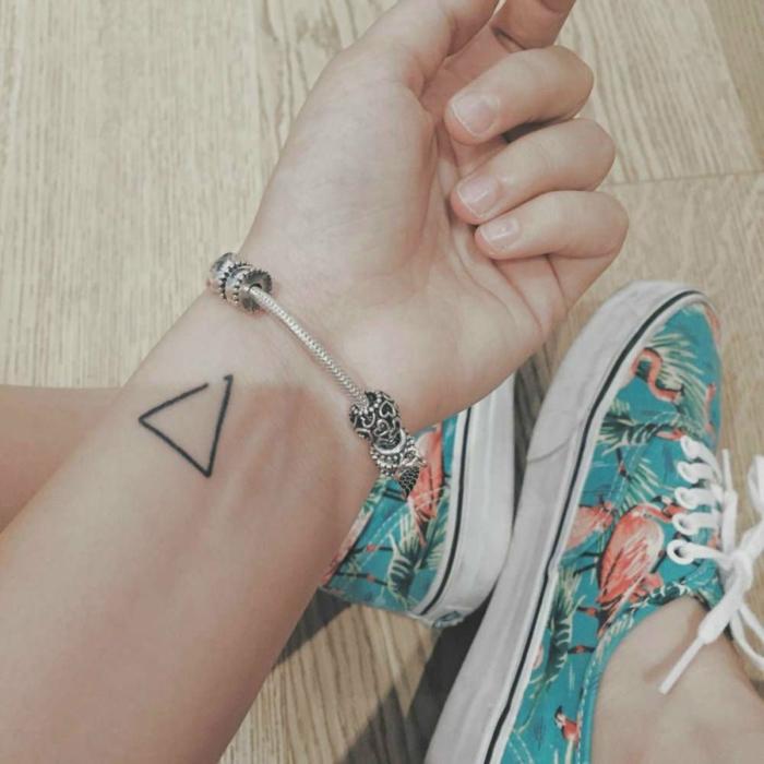 mujer con zapatillas en flamencos, pulsera pandora, tatuaje minimalista de triángulo incompleto, tatuajes flechas