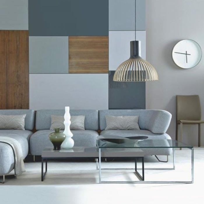 estilo nordico, pared decorada con paneles en tonos grises, mesita de vidrio, reloj redondo, lámpara colgante, decoracion habitacion