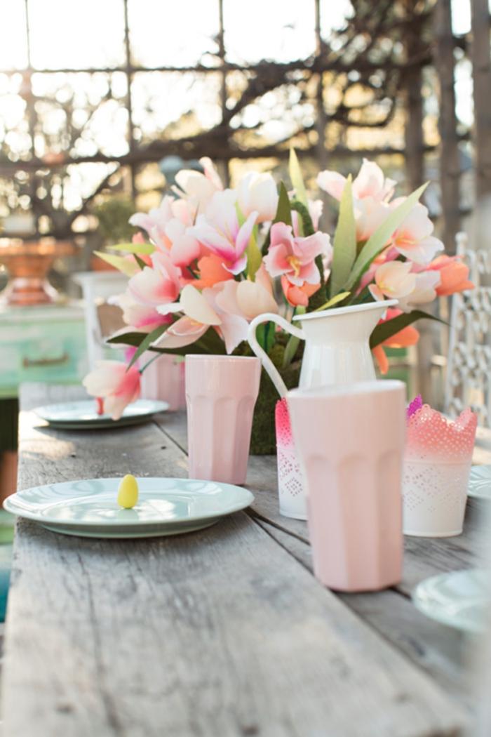 centro de mesa en colores pastel, bonita decoración de flores y pequeños huevos pintados en amarillo, jarrones en color rosa