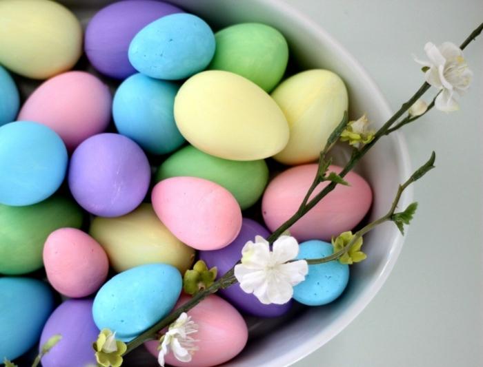 huevos de encanto pintados en colores pastel, huevos coloreados en azul, lila, amarillo y rosado, decoración con ramos de árboles
