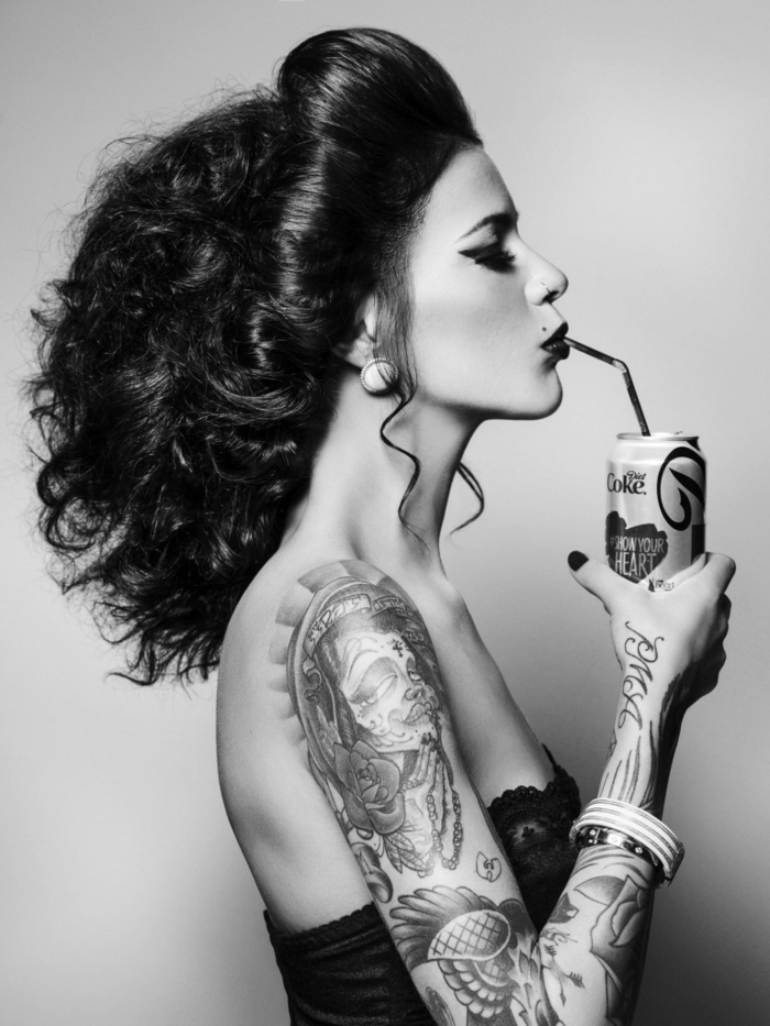 diseños de tatuajes para mujeres, mujer con pelo rizado negro con mucho volumen y brazo tatuado con tinte negro