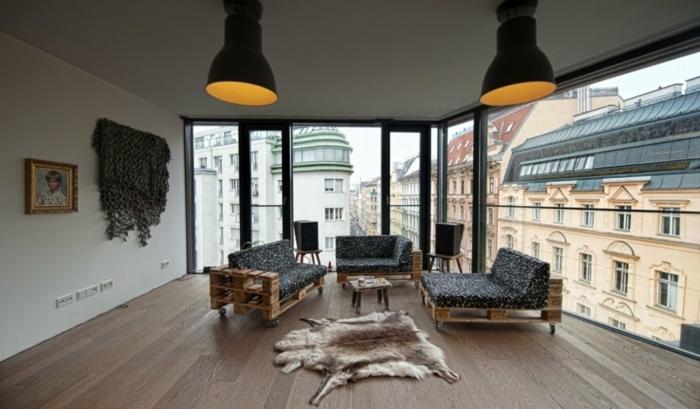 bonito salón con grandes ventanales con vista y sillones con palets, sillones tapizados en negro y blanco y suelo de parquet