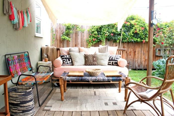 bonita decoración de jardín con muchos elementos decorativos y sillones con palets, sofá en color rosa con cojines coloridos