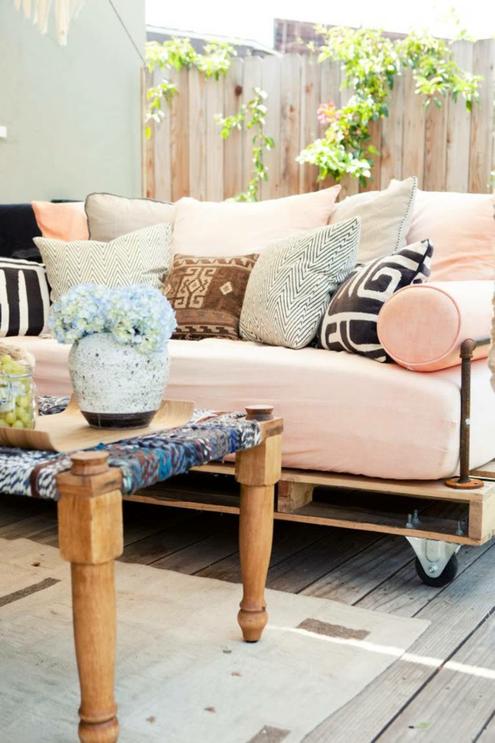 ideas de encanto de decoracion con palets, sofá en color rosa hecha de palets de madera, cojines decorativos con estampados
