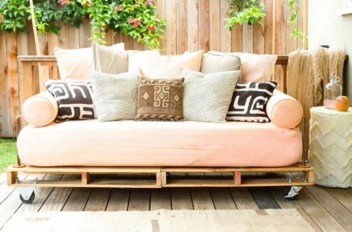 sillones con palets de encanto, jardín decorado con sofa en color rosa en ruedas hecho de palets y muchos cojines decorativos