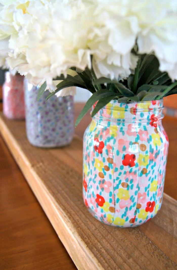 decoración hecha de mano de un frasco de vidrio, jarrón decorativo DIY con dibujos de pequeños flores coloridos, manualidades con botellas de cristal y tarros