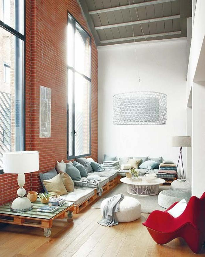 salón de encanto con muebles de palets, decoración moderna con paredes blancos y pared de ladrillos, cojines decorativos en colores pastel